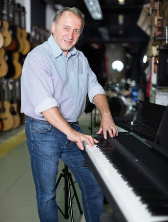 Smiling musician is playing on modern keyboard in music shop.