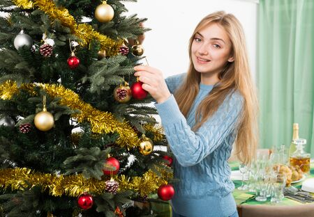 Smiling blonde girl arranging decorations of Christmass tree