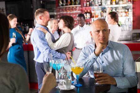 Hombre de negocios preocupado sentado en la mesa, sin divertirse en la fiesta corporativa en el bar