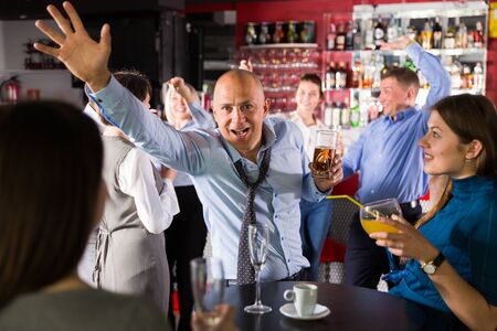 Portrait of man in unbuttoned shirt dancing at corporate party Imagens
