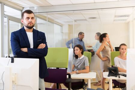 Portrait of confident adult businessman with arms crossed in busy modern coworking space