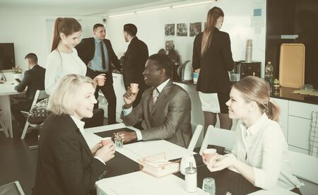 positive international young group of business people chatting while enjoying coffee in break room