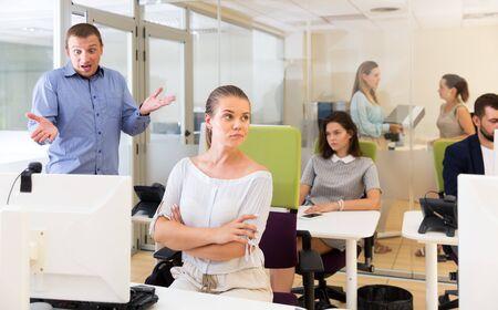 Empresario descontento expresando su insatisfacción con el trabajo de una joven frustrada en la oficina moderna Foto de archivo