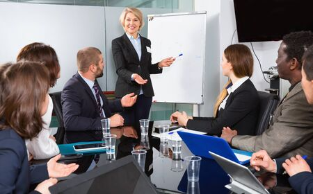 Elegant cheerful positive glad mature businesswoman discussing new project with his team in meeting room