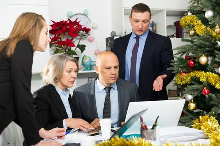 Successful coworkers engaged in business activities at common table in office Stock Photo