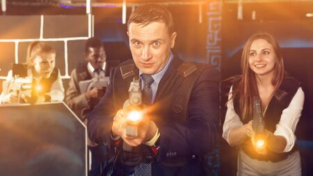 Man in a business suit holding the his laser gun and playing laser tag with colleagues Banco de Imagens