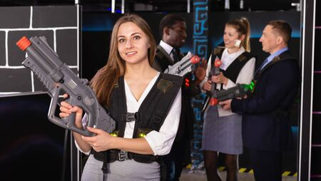 Woman in the business suit holding the laser gun and playing laser tag with colleagues Banco de Imagens