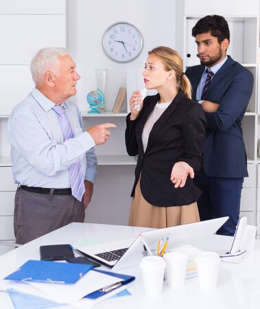 Mature boss is chastising employees because of uncompleted work in the office.