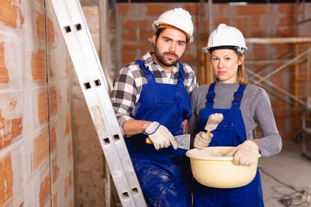 Portrait of two painters inside a cottage under construction
