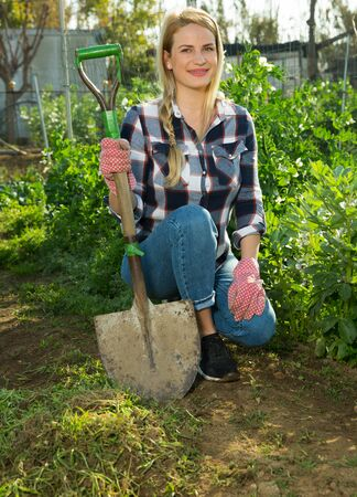 Young female farmer working with hoe in vegetable garden