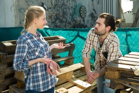 Cheerful couple talking near wooden pallets at organic farm