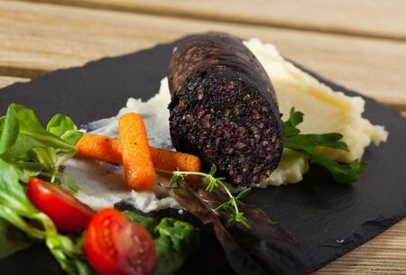 Black pudding with rice served with potato puree, vegetables and greens