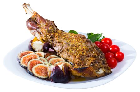 Gigot baked in oven with honey, served with fig, Feta cheese and herbs. Isolated over white background