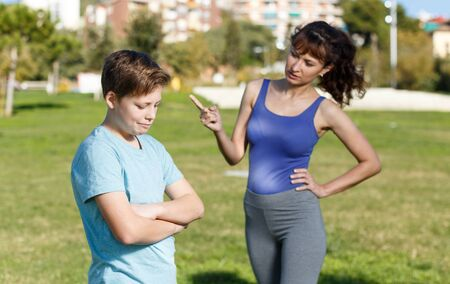 Portrait of upset teen boy in sportswear scolded by mother at sports ground