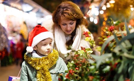 Happy school age boy with mother selecting decoration for home on Christmas market Stock Photo