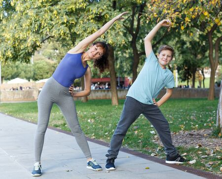 Happy family of mother and preteen son stretching together during training outdoors Фото со стока