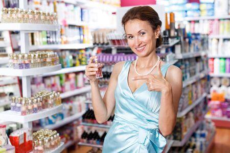 Cliente mujer sonriente en vestido azul elegir perfume en tienda de cosméticos Foto de archivo
