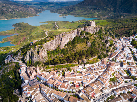Aerial view of Zahara de la Sierra city with fortified castle on rocky hill on background