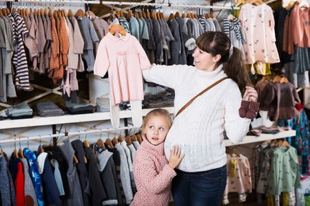 Cheerful pregnant mother and daughter choosing clothes for baby in children's cloths store. Focus on girl
