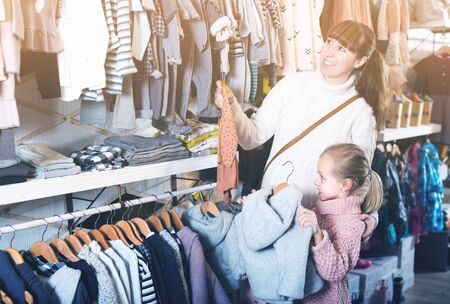 Pregnant mother and daughter choosing clothes for baby in children's cloths shop