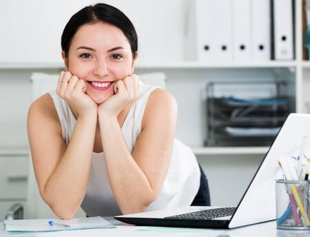 Smiling woman manager posing at ease sitting in office