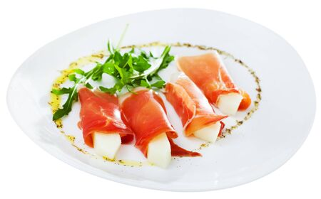 Spanish tasty dish rolls of prosciutto di parma with melon served with arugula at plate, close up. Isolated over white background Stock Photo
