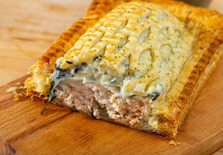 Delicious puff pastry pie with fish filling from salmon and cream sauce