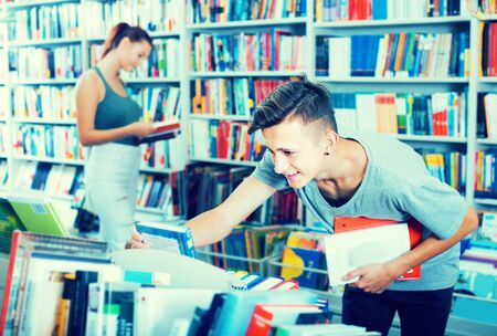 Cheerful teenager boy looking for new book on shelves in store Imagens