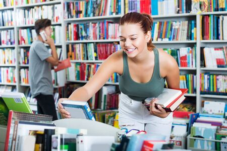Smiling young teenager girl looking for new literature on shelves in book store