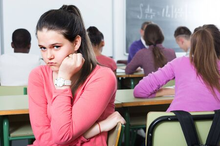 school pupil sitting away from classmates and feeling depressed indoor