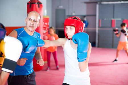 Boxing instructor controls the sparring between the two boys in the gym Archivio Fotografico