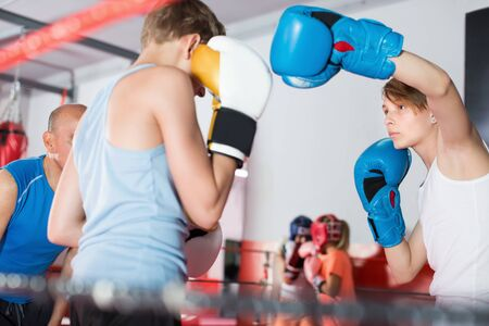 Young sportsman exercising at boxing with coach on boxing ring