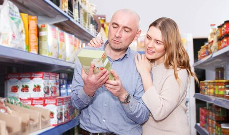 Portrait of smiling couple  customers looking groats in  grocery food shop