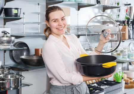 Smiling woman is choosing new stewpot for her house in the shop