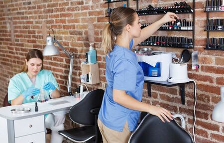 Young smiling girl manicurist standing at her workplace in modern the nail salon Stock Photo