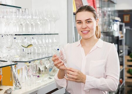Young smiling woman buying glassware in cookware shop Stockfoto