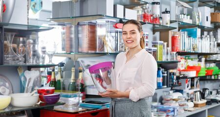 Smiling positive young woman buying ware for wine bottle in cookware shop