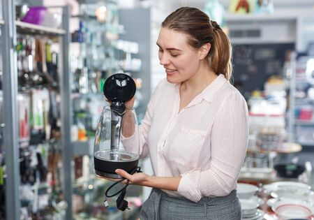 Young female housewife buying electric kettle in kitchen appliances section