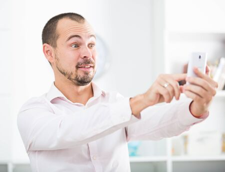 Young happy european businessman in office playing with smartphone