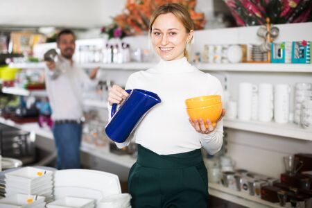 Positive couple choosing new crockery in dinnerware store