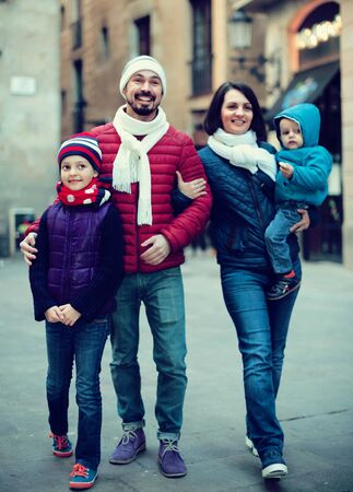 Positive family walking in casual clothes at winter day