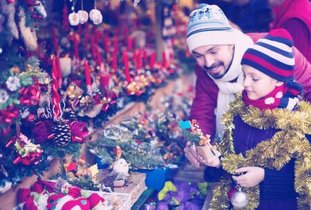 spanish little girl with dad buying decorations for Xmas. Focus on girl