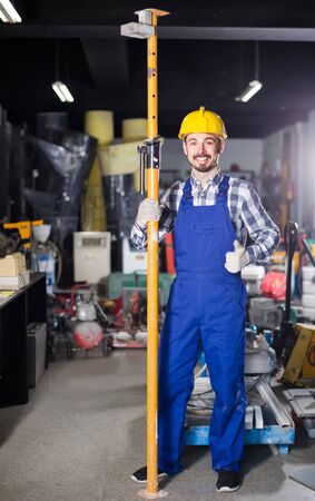 happy european working man practicing his skills erect trestle at workshop