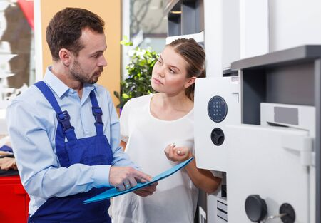 Man in blue overalls showing catalog of safes models to adult female client in store