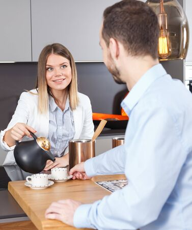 Happy young woman pouring coffee to her male guest in modern kitchen interior 免版税图像