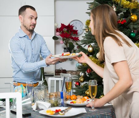 Loving couple cleaning together table with plates and glasses after Christmas dinner