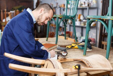 Professional young man carpenter repairing antique furniture in workshop