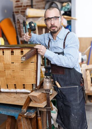 Professional male carpenter upholstering vintage armchair in repair shop Reklamní fotografie