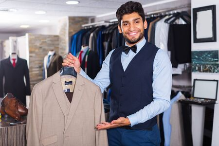 Male customer demonstrating his choice of suit in apparel shop