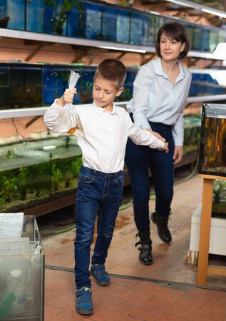 Cheerful teen boy holding plastic bag with tropical fish bought with his mom in pet shop